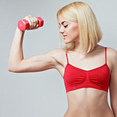 young woman lifting dumbbells on grey background