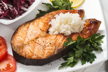 Grilled trout with vegetables and rice. Close-up