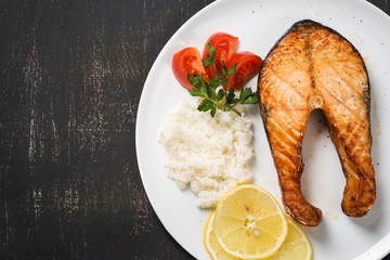 Top view of baked trout with vegetables and rice. Space for text