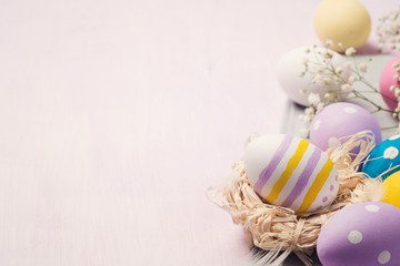Colorful Easter eggs on a wooden table with space for text