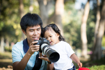 Father and daughter looking picture on camera in the park