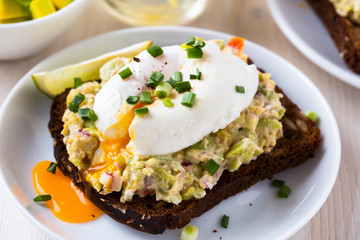 Avocado and feta smash on rye bread and poached  egg on top