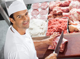 Confident Butcher Cutting Meat At Counter