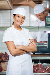 Confident Butcher With Colleague Working In Store