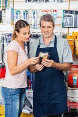 Salesman Assisting Customer In Buying Flashlight At Store
