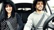 Boy driving car making cute girl laugh showing dance