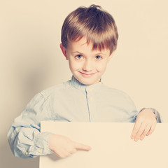 Smiling little boy with empty paper blank in hands