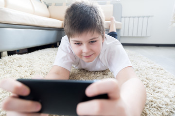 boy with  phone lying on a carpet in the room