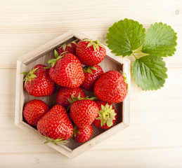fresh ripe strawberries and wet leaves on wooden background
