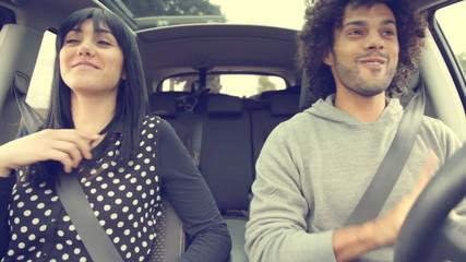 Handsome man driving car making girl dance funny