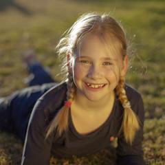 Retrato de niña rubia de ojos verdes con trenzas