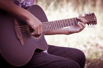 Male hand playing acoustic guitar on meadow background in retro