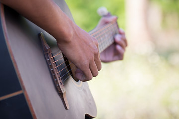 Male hand playing acoustic guitar on meadow background