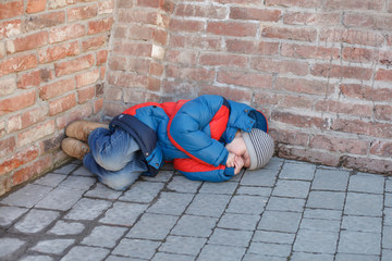 homeless boy leaned against the wall