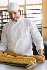 Baker looking at freshly baked baguettes