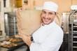 Smiling baker holding bag of flour - 78359022