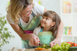 mother and daughter cooking and cutting vegetables on kitchen - 78359091