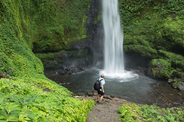 Man standing by lush green Jungle waterfall in Indonesia