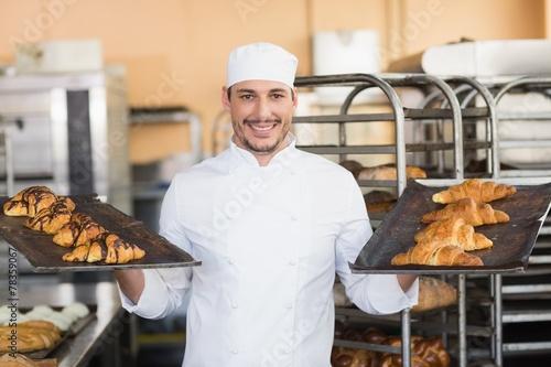 Papiers peints Table preparee Smiling baker holding trays of croissants