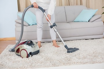 Woman using vacuum cleaner on rug