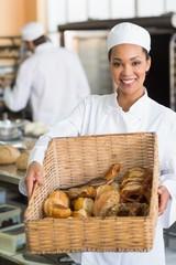 Pretty baker showing basket of bread