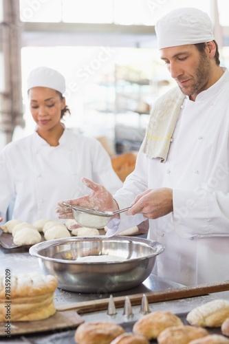 Leinwanddruck Bild Baker sieving flour into a bowl