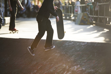 Anonymous skateboarder with skateboard at a skate park
