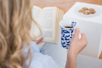 Blonde sitting on couch reading with cup of coffee