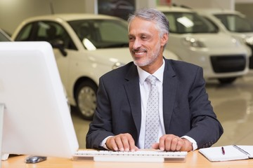 Cheerful businessman working at his desk