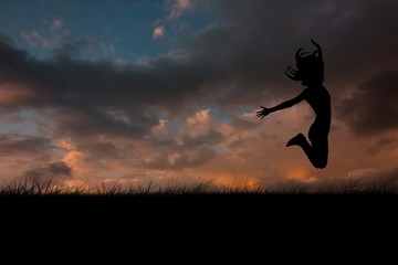 Composite image of silhouette of woman jumping