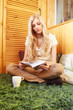Young blonde woman sitting on green carpet with book
