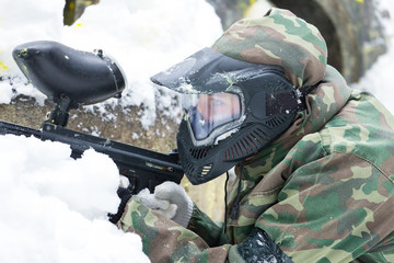 Closeup of paintball player in mask in winter