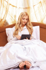 Young happy  blonde woman in the bed