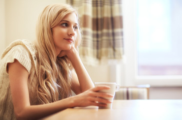 Young blonde woman with coffee cup at the table