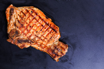 steak of beef grilled on a black background
