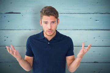Composite image of handsome young man shrugging shoulders