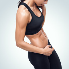 Sporty woman in a gym showing her well trained body