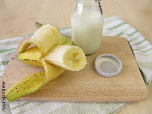 Leinwandbild Motiv Eine Flasche Kefir mit Banane
