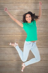 Composite image of pretty brunette jumping and smiling
