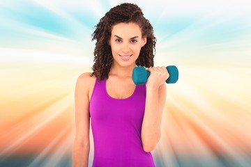 Composite image of fit woman lifting blue dumbbell