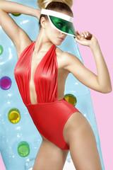 Stylish blond girl posing wearing  beachwear and sunshade