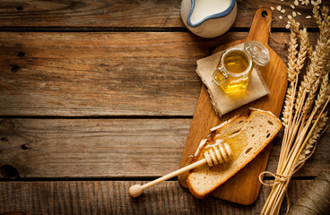 Honey in a jar, slice of bread, wheat and milk on vintage wood
