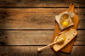 Honey in a jar, slice of bread and honey dipper on vintage wood