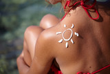 Woman With Suntan Lotion At The Beach In Form Of The Sun