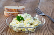 Leinwandbild Motiv Kartoffelsalat in einer Glasschale auf Holz