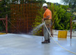 Construction worker watering fresh concrete slab using a hose - 78364806