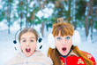 two girls surprised faces on snow background