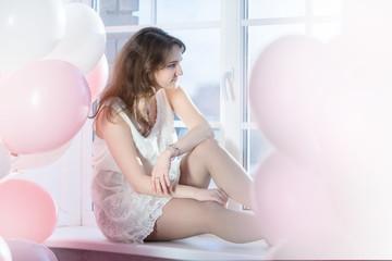 thoughtful girl sits down on a windowsill