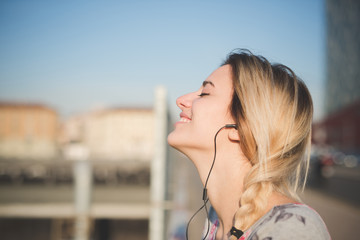 young beautiful blonde woman outdoor listening music