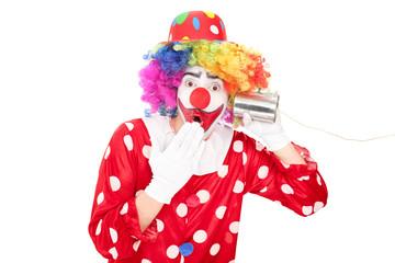 Surprised clown listening through a tin can phone